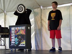 Comedy magician Jerry Frasier (and volunteer) performing at Riverfront Rendezvous, Pfiffner Pioneer Park, South Tent, Stevens Point, WI  07/04/2014 3:52PM (Craig Walkowicz) Tags: wisconsin comedy magic optical illusion volunteer magician stevenspoint jerryfrasier riverfrontrendezvous