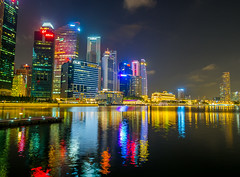 A City by the Light Divided... (Dinozauw) Tags: marinabayfinancialcentre singapore lights night cityscape city cbd centralbusinessdistrict reflection marinareservoir waterfront water colour color colourful marinabay collyerquay buildings southeastasia architecture outdoor urban mzuiko12mmf20 jetty skyline downtown bright towers ntuc oue hsbc evening illuminated illumination cliffordpier thefullertonbayhotel vivid