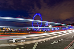 London Eye at Night (david gutierrez [ www.davidgutierrez.co.uk ]) Tags: city uk longexposure travel bridge blue light sky urban bus colors westminster night clouds photography noche movement perspective londoneye wideangle landmark fisheye le londres lighttrails iconic londra streaminglights davidgutierrez pentaxk5