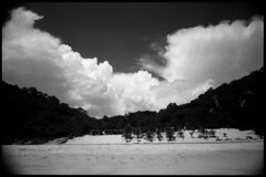 Grainy, High Contrast Black and White Beach Photograph. (axlright) Tags: ocean blackandwhite film beach clouds contrast dark mexico dramatic highcontrast grainy 3200 25a