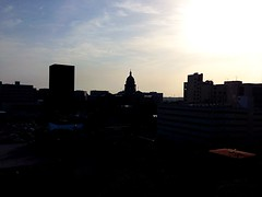 Sunrise Over the Texas State Capitol (Cesar's iPhoneography) Tags: cameraphone city morning windows sky sun cars silhouette skyline clouds sunrise buildings austin morninglight downtown cityscape texas skyscrapers rooftops parkinggarage cloudy horizon capitol dome parked tall stories skyward parkedcars magichour atx iphone texascapitol shadowy texasstatecapitol goddessofliberty texascapital stategovernment iphoneography