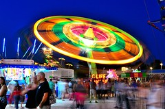 Cliff Hanger (mitchell_vanerdewyk) Tags: longexposure carnival blue light red lightpainting color green yellow dark painting downs flying lyon crowd trails fair ups rides lighttrails countyfair saucer peoplewatching fairrides lyoncounty
