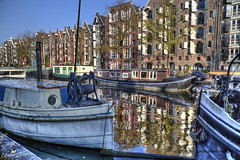 Reflections in Amsterdam (Jan Kranendonk) Tags: holland dutch amsterdam canal boats houses buildings sunny autumn fall water historical old sky street travel city landmark scenic corner netherlands reflection flag warehouses homes apartments houseboats gracht boten reflectie weerspiegeling spiegeling grachtenpanden grachtengordel