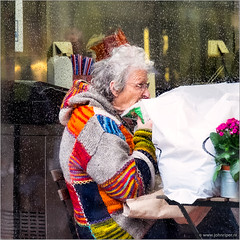 Colourful autumn scene (John Riper) Tags: johnriper street photography straatfotografie square vierkant netherlands candid john riper fuji fujifilm xt1 18135 coolsingel autumn chequered colors colours fall flowerpot old lady woman eating bag raindrops glass window jumper sweater table restaurant terrace reflection