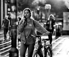 Summer rain (graveur8x) Tags: summer rain girl woman candid street portrait dof blackandwhite frankfurt germany schwarzweis bw streetphotography light contrast people city bicycle wet cellphone sun olympus olympusem10markii olympusm75mmf18 75mm zuiko microfourthirds m43
