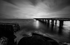 Crashing in (Laws Photography | www.lawsphotography.com) Tags: ocean longexposure blackandwhite bw seascape monochrome clouds canon landscape photography pier movement rocks flickr horizon fineart tripod australia victoria seawall le pilings endoftheday neutraldensityfilter benro blackandwhitefineart nd10stop nd1000nd400