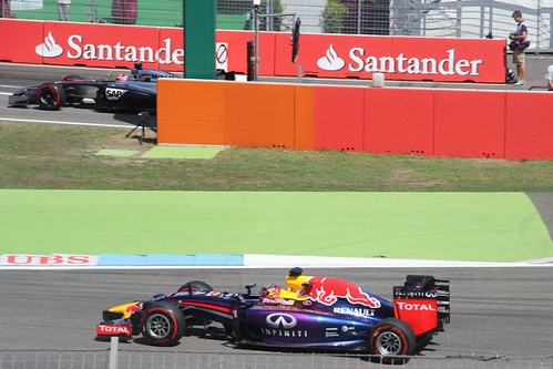 Sebastian Vettel's Red Bull completes a lap as a McLaren comes out of the pits at the 2014 German Grand Prix