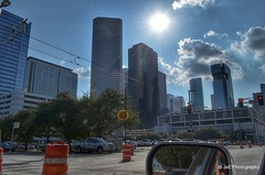 Downtown from Capitol and Crawford (elnina999) Tags: park plaza new city travel blue trees windows sky urban panorama cloud reflection building cars window glass lamp skyline architecture modern skyscraper fence buildings circle corporate drive office high highway downtown day commerce cityscape texas exterior view traffic cloudy district famous platform houston sunny landmark center panoramic business round infrastructure metropolis tall shape finance nikond5100