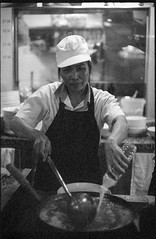 Thai smile (waex99) Tags: 2016 50mmf14 bw c41 f filmneverdiecom ruby singapore film nikon nov nikonf analog argentique slr 50mm blanc white noir shikuro shirokuro underexposed under goosen food cook woman thai republic orchard work workers kitchen hawker wok grain