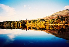 autumn hues (fotobes) Tags: lake water blues sky reflections reflection trees leaves mountain yacht boat lca lomo expiredfilm xpro crossprocess crossprocessed grain colours shoreline lakedistrict unitedkingdom coniston lakeconiston conistonwater