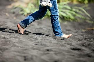 Feet on black sand beaches of Vík