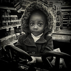 """She Was Driving Her Racing Car Around the Food Market, """"The Soul Is Healed By Being With Children"""", Woodbridge, Virginia (Gerald L. Campbell) Tags: streetphotography street squareformat spirituality socialdocumentary bw blackwhite citylife community digital dc washingtondc woodbridge girl kids love portrait portraitphotography virginia youth yearning yeswecan iphone6splus"""