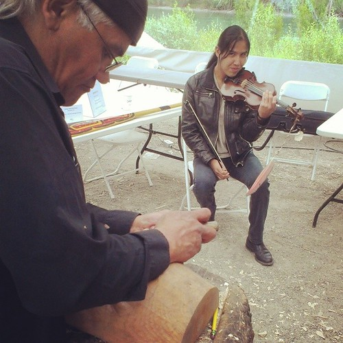 Master Tlingit carver Wayne Price at work while #NWT fiddler Wesley Hardisty entertains at Adäka festival demo tent #yxy #Yukon