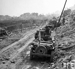 Amid ruins, the jeeps of a medical outfit line roadside awaiting wounded during the Allied push to take the town of Cassino, Italy, February 1944