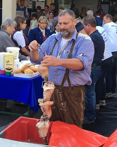 #OctoberFest cook loading #pigsFeet to a #BBQ skewer - check out the #lederhosen