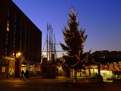 Christmas tree on Brunel Square with the ss Great Britain in the distance (chibeba) Tags: bristol winter 2016 december city england english urban southwest southwestengland britain greatbritain europe harbourside harbour bristolfloatingharbour christmas christmastree brunelsquare historic cobbles heritage twilight evening