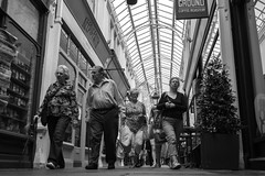 Indoor Arcade (Howie Mudge LRPS) Tags: cardiff caerdydd people men women shops shopping shoppers windows doors glass roof ceiling signs inside indoors ally mall candid portrait casual travel travelling traveler wales cymru uk compactcamera blackandwhite blackwhite mono monochromatic monochrome street streetlife streetphotography urban urbanphotography