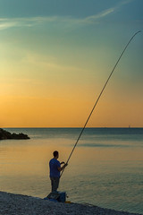The early bird catches the fish (France through my eyes) (docoverachiever) Tags: france man beach ocean fishingpole mediterraneansea water person candid 101116 nice sunrise fishing fisherman