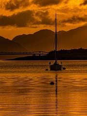 Yacht at Sunset on Loch Leven (Bill M9) Tags: sunset orange reflection water scotland boat yacht glencoe lochleven fz150