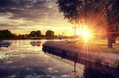 A Sunstar Bend (henriksundholm.com) Tags: park city bridge trees sunset sky sun sunlight lake water grass clouds reflections landscape sweden lilies sverige railing beams hdr eskilstuna sunbeams waterscape sunstar stadsparken eskilstunan nybron lightstar