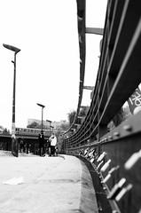 Berlin bridge in black and white (Hammerhead27) Tags: oberbaumbrucke lamp train blackandwhite mono bw sidewalk floor curve pov low concrete road lock rail people photographer street bridge germany berlin