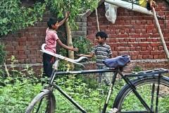 Thanks for sharing! (Pejasar) Tags: boys siblings brothers india delhi sharing gift food bicycle