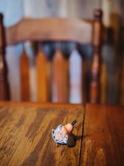 Disembodied (BurlapZack) Tags: olympusomdem5markii panasonicleicadgsummilux25mmf14 vscofilm pack01 paristx arthurcitytx actionfigure disembodied decapitated beheaded table family visit availablelight handheld bokeh dof woodgrain chair dinnertable toy chidhood relatives cousins microfourthirds