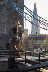 Girl with a Dolphin (and a bridge and a Shard) (Spannarama) Tags: contrejour flare sunlight sunshine lowsun london uk towerbridge bridge shard goldenhour fountain water dolphin sculpture thames river