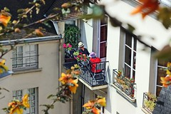 Afternoon Delight (Jan Nagalski) Tags: flowers red sun paris france cute sunglasses yellow vines afternoon shadows apartment friendship balcony hats sunny elderly shade spycam cityscene companionship seniorcitizen afternoondelight elderlycouple jannagal jannagalski