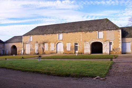 Des bâtiments d'exploitation aux toits de lave, restes de l'ancienne basse cour, entourent la grande cour extérieure et servent d'avenue d'honneur en avant du portail.