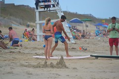 Surfing Lesson (Tobyotter) Tags: man beach northcarolina nagshead surfboard outerbanks womanswimsuits