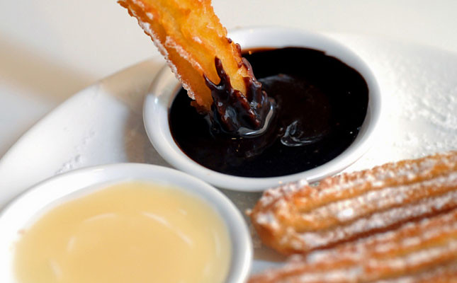 Warm Spanish churros donut with dark chocolate sauce