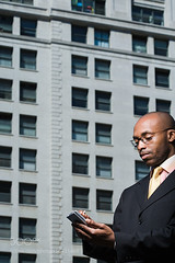 Businessman using handheld computer (ABulimia159) Tags: african ethnicity wireless technology people blue city usa man urban male new york adult north america one person building day business looking outside standing vertical office tie structures photograph serious american concentration living clear sky communication real busy holding smart suit businessman organization confidence eyeglasses on the go white collar hitech taking a break half length individually mid handheld computer