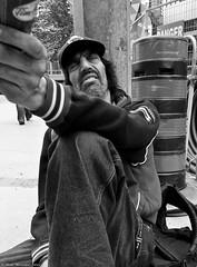 Close Encounters. (Neil. Moralee) Tags: neilmoraleenikon canada man beg begging beggar begger beger panhandle poverty street candid poor black white bw blackandwhite mono monochrome hat sitting kerb sidewalk pavement homeless desperate junky junkie drug habit addict addiction beard aggressive cocaine crack rush weed skunk marijuana smack skag horse h gear brown nikon zoom neil moralee d7000 18200mm