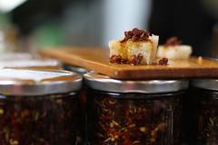 A tasty blend... [Explored] (judi may) Tags: wood red food london canon bread dof bokeh explore boroughmarket 7d jar jars breadboard blend foodtasting explored fluidrexplore theweeklyalphabetchallenge