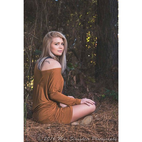 Girl-next-door Cheyenne sitting indian style on a bed of pine needles out in the woods. She is a cutie.