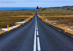 The highway to Kirkjufell. (Pete 5D...©...) Tags: highway iceland west coast tarmac sea ocean water horizon sky blue mountain hill rock formation leading lines empty white yellow post posts
