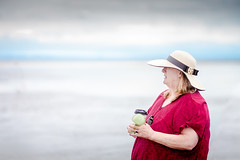 the lady wearing a hat (michaelinvan) Tags: lady woman summer beach hat waterbottle sunglasses sand water cloud sky horizon red canon5d2 135mm f2 daytime existinglight delta boundarybay negtivespace composition senior people portrait coffeecup naturallight canada vancouver