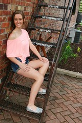 Smiling on the Fire Escape (PhotoAmateur1) Tags: old morning pink blue red portrait woman brown brick feet beautiful beauty smile face smiling wall shirt stairs silver hair neck skinny outside outdoors nose fire photography am spring model eyes shoes long sitting escape photoshoot arms legs sweet head top background gorgeous country steps young stomach lips jeans tummy denim shorts brunette lovely thin shoulder throat photosession slender collarbone daisydukes