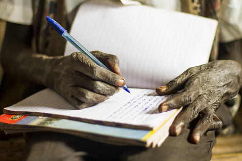 A refugee student writes notes in makeshift classroom