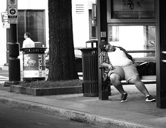 Waitin on the Bus (Philip Osborne Photography) Tags: street photography obese man black sleeping bustop bw cap charlotte nc tryon