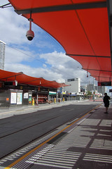 Waiting for the Tram (Jocey K) Tags: australia queensland southport goldcoast tramstationshadowspeopleskycloudslinesbuildingsarchitecturesecuritysystem