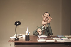 Señor de verde sobre fondo beige. (elojeador) Tags: figura exposición plastilina mesa escritorio escritor migueldelibes flexo lapicero libro gafas escultura beige elojeador