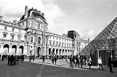 The Louvre with Pyramid and Tourists (EmperorNorton47) Tags: paris iledefrance france photo analog film nikonn8008 nikonn801 fomapan100 autumn fall blackandwhite thelouvre pyramid palace architecture impei