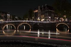 Amsterdam Canal (kar1187) Tags: amsterdam city break canal water way lights night evening dark bright motion red light bikes bridge tunnel buildings brick lines