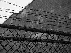 It keeps us from them...(B&W) (L.M. Brown) Tags: fense black white monochrome brick barbed wire moline lmbrown lm brown poor street photography photojournalism