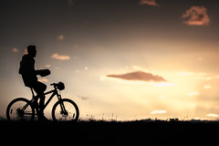 Riding into the sunset (michaelinvan) Tags: sunset backlight backlit people biker bike handoff silhouette againstlight handlebar spoke downtheroad richmond cloud interestingcloud grass susettime fall autumn paddle boy man road travel outdoor exercise vancouver canada trail westdyke terranova contrast lowlight bokeh dof