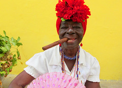 Cuban Woman with Cigar (shaire productions) Tags: cuba cuban image picture travel world culture cultural building caribbean outdoor photo photograph photography portrait woman cigar yellow red bright lady female smile smiling vibrant strength personality smoking smoke imagery traveler street urban naturallight canon
