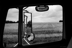 I see everything.  Too bad I wasn't watching the road... (Attic Light) Tags: blackandwhite truck landscape drops highway harvest farmland