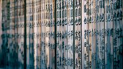 Kehi Jingu repetition (Eric Flexyourhead) Tags: tsuruga tsurugashi  fukuiken  japan  kehishrine kehijingu  detail fragment shrine shinto wood wooden weathered worn characters kanji repetition shallowdepthoffield bokeh 169 olympusem5 mzuikodigital75mmf18 75mm zd